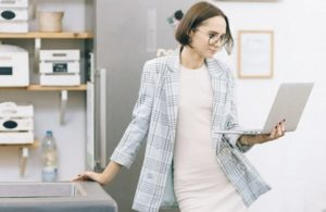 Business casual woman leaning on one arm against work table while holding an open laptop and reading from it with the other arm