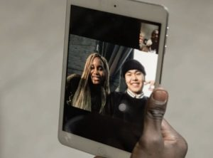 Hand holding up tablet device of a young man and woman smiling with a small picture-in-picture of a man and colleagues